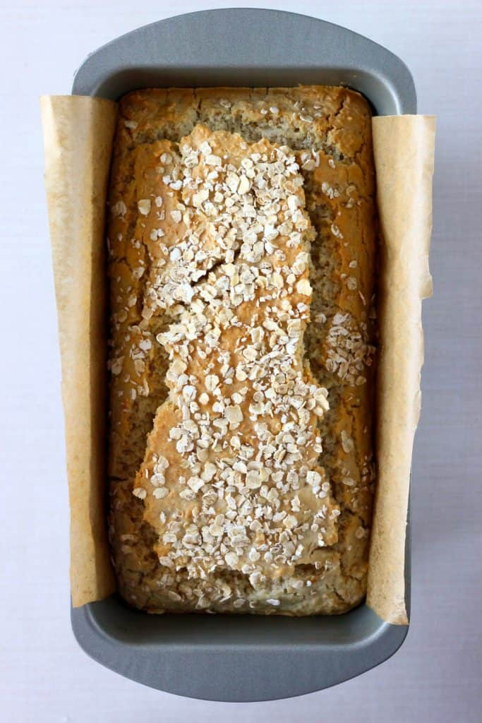 A loaf of golden brown bread topped with oats in a silver loaf tin lined with brown baking paper against a white background