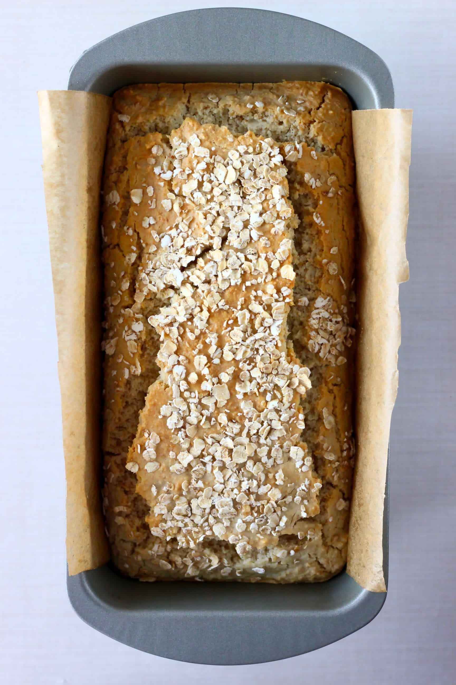 A loaf of gluten-free vegan oat bread topped with oats in a loaf tin