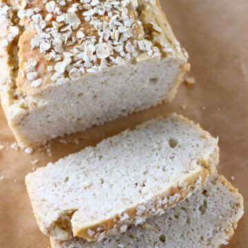 A loaf of gluten-free vegan oat bread topped with oats with two slices on the side