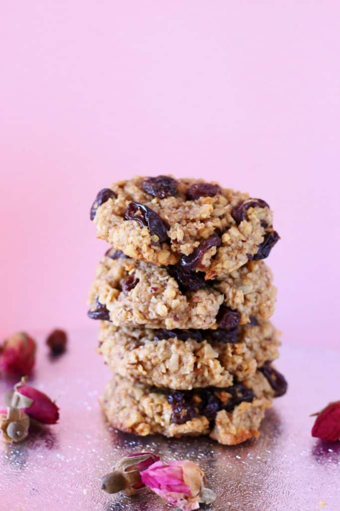 Four oatmeal raisin cookies stacked on top of each other against a pink background