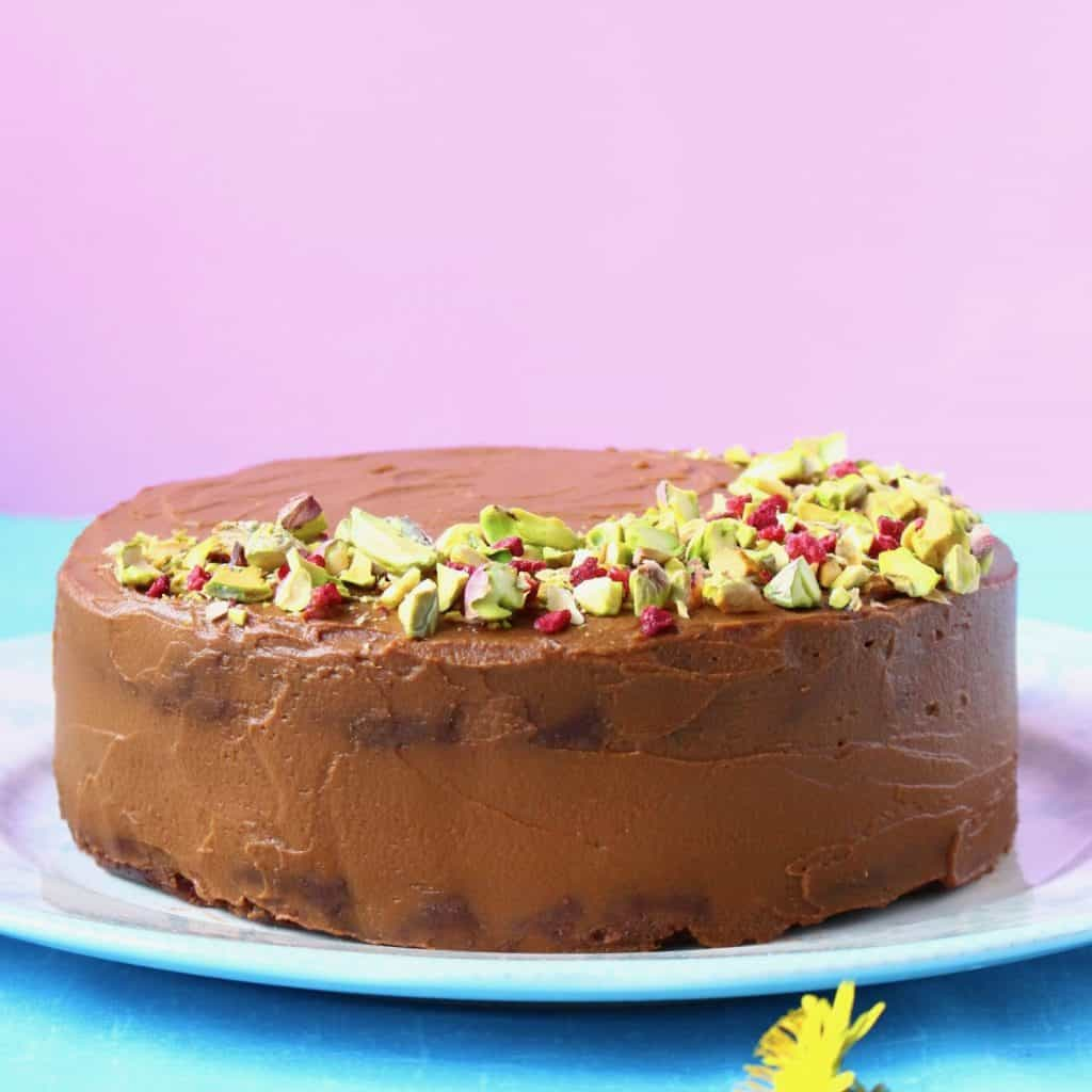 A chocolate cake topped with chopped pistachios and freeze-dried raspberries on a blue plate against a pink background