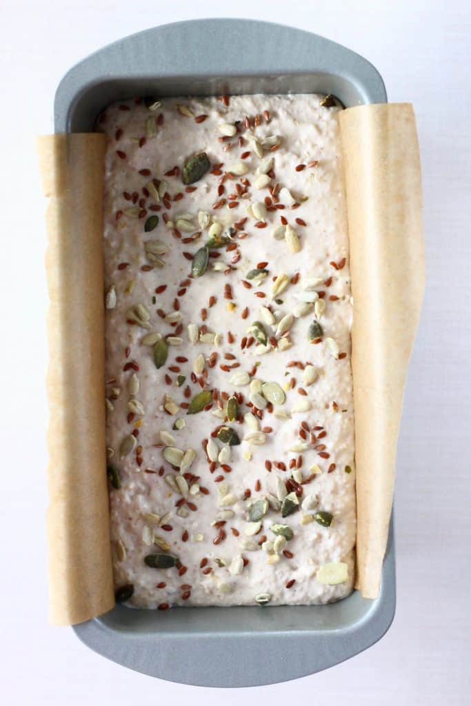 White bread batter scattered with mixed seeds in a silver loaf tin lined with brown baking paper against a white background