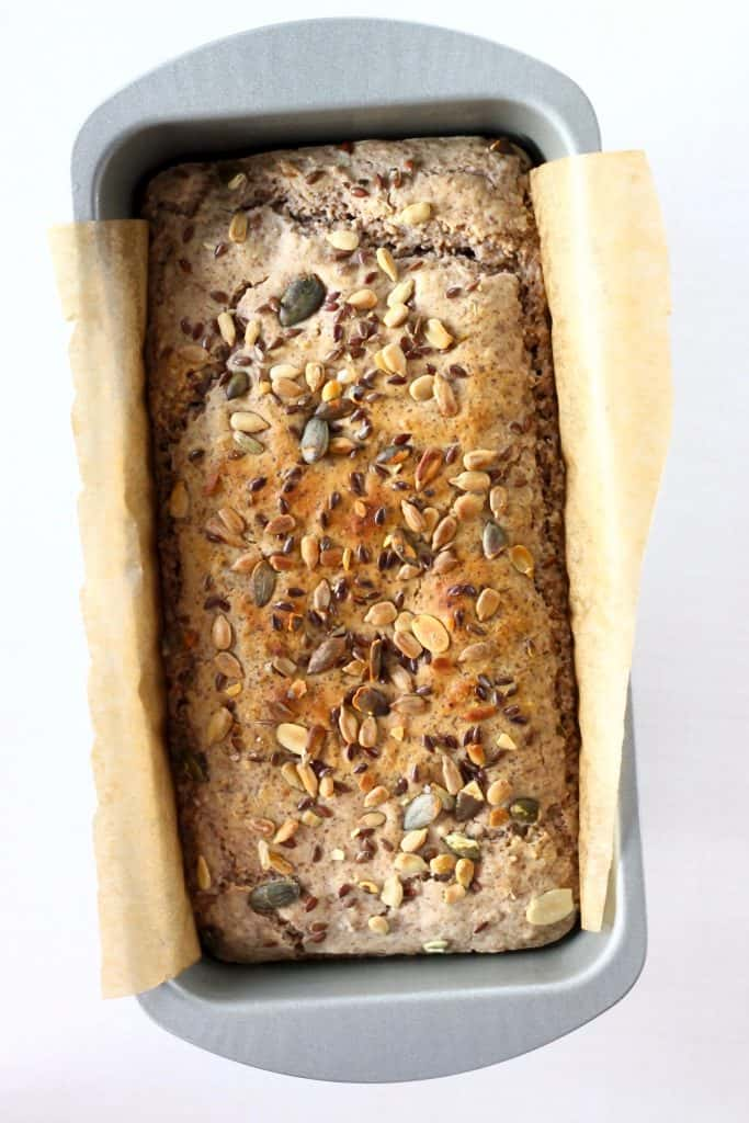 A loaf of golden brown bread topped with mixed seeds in a silver loaf tin lined with brown baking paper against a white background