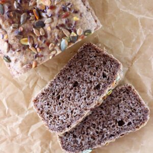 A loaf of brown bread topped with mixed seeds with two slices next to it against a sheet of brown baking paper