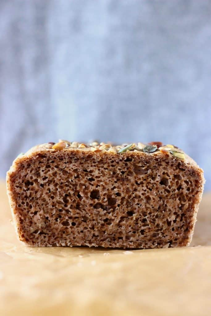 A sliced loaf of brown bread on a sheet of brown baking paper against a grey background