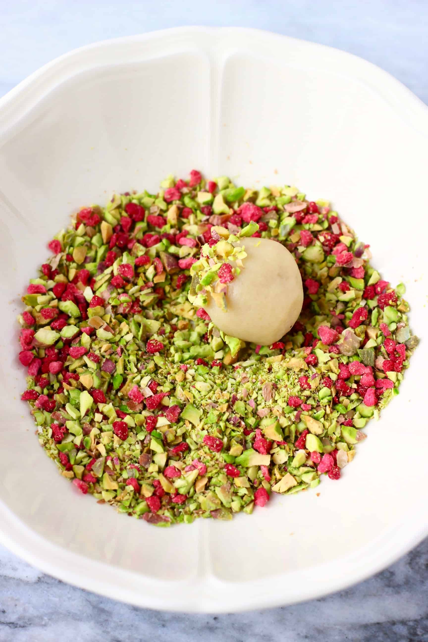A vegan white chocolate truffle being rolled around in a bowl of chopped pistachios and freeze-dried raspberries