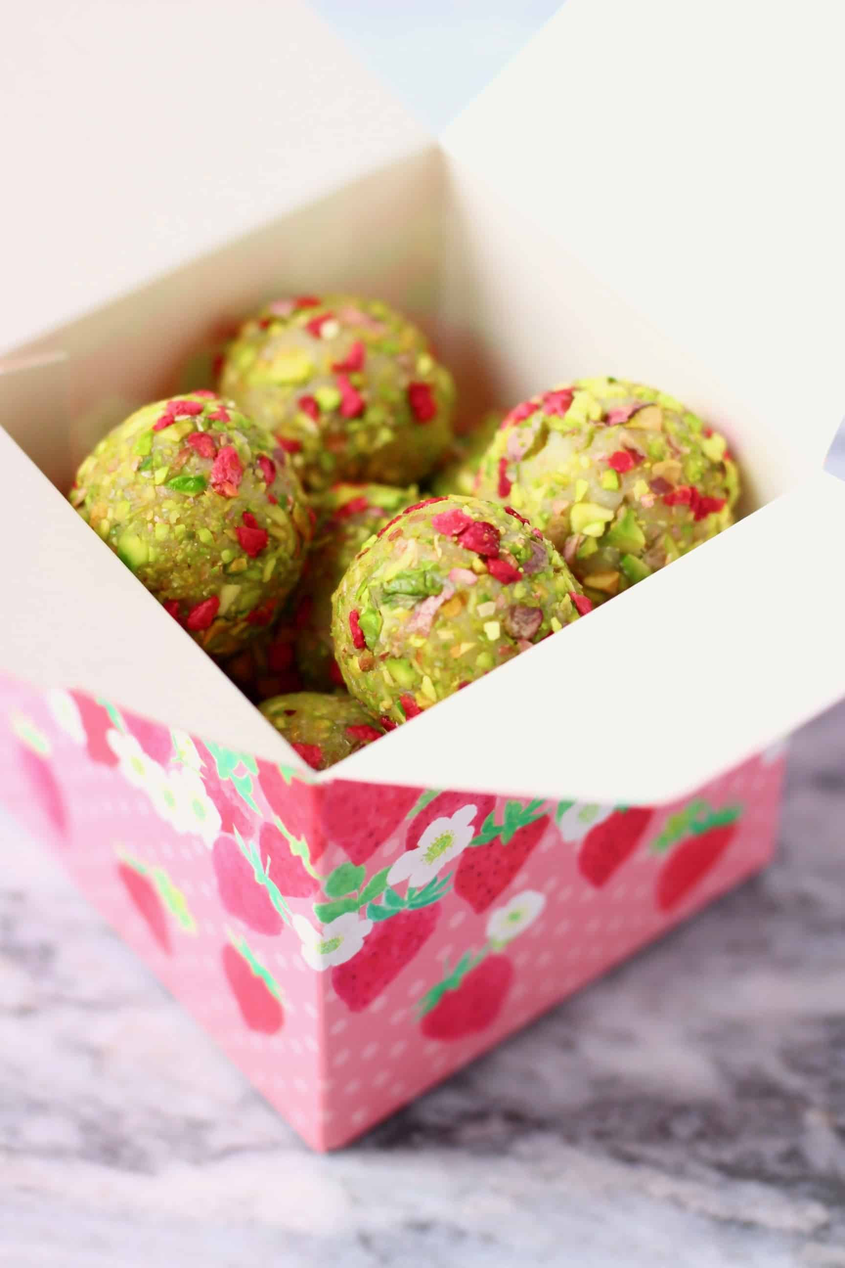 Vegan white chocolate truffles covered with chopped pistachios and freeze-dried raspberries in a small pink gift box