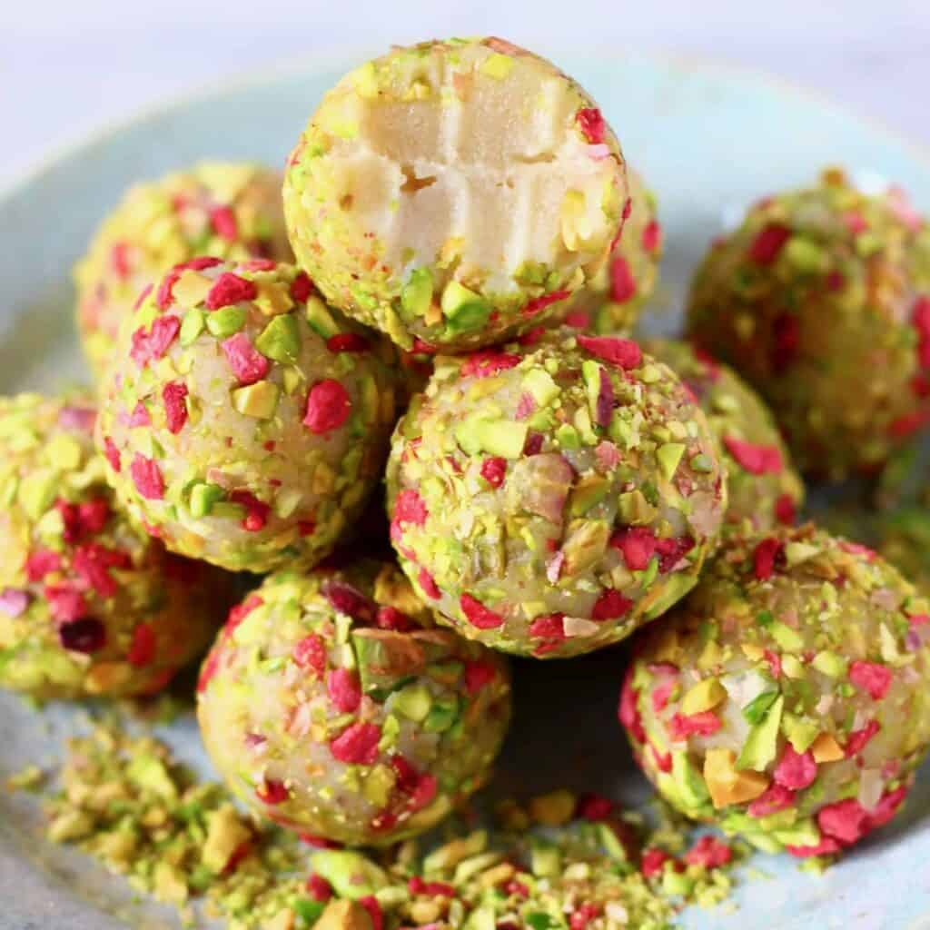 A pile of white chocolate truffles covered in chopped pistachios and freeze-dried raspberries with a bitten one on top on a light blue plate against a marble background