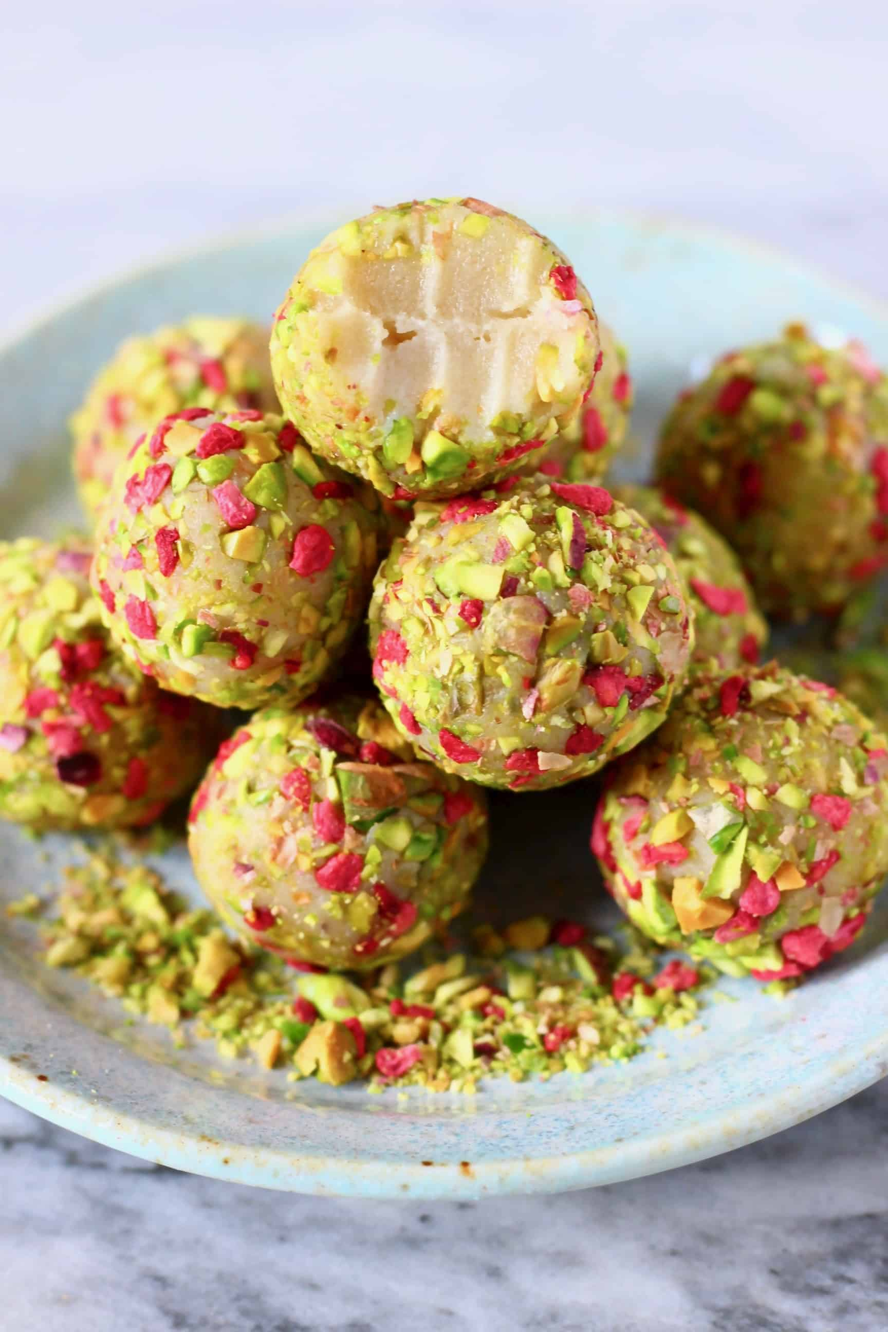 A pile of vegan white chocolate truffles covered in chopped pistachios and freeze-dried raspberries with a bitten one on top