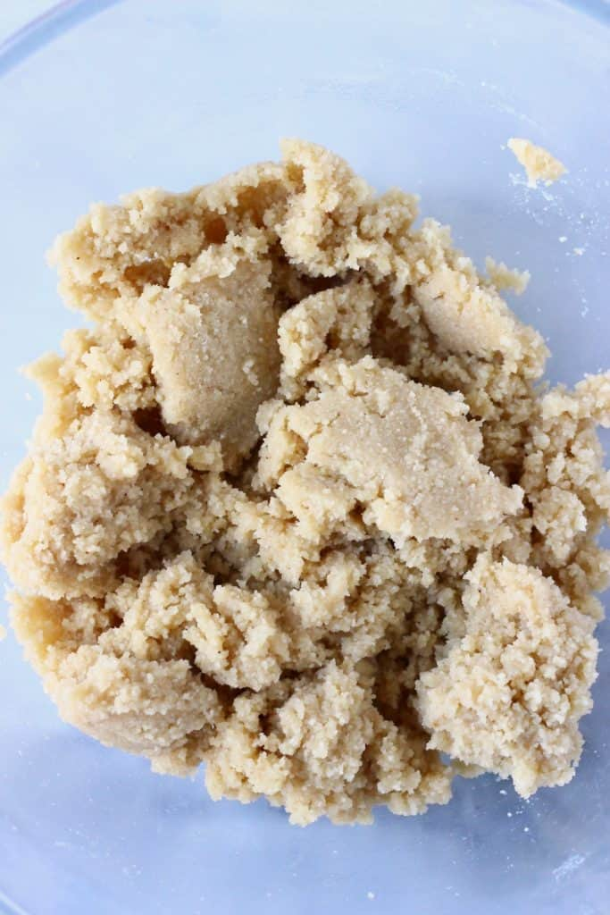 Raw shortbread cookie dough in a glass mixing bowl against a marble background