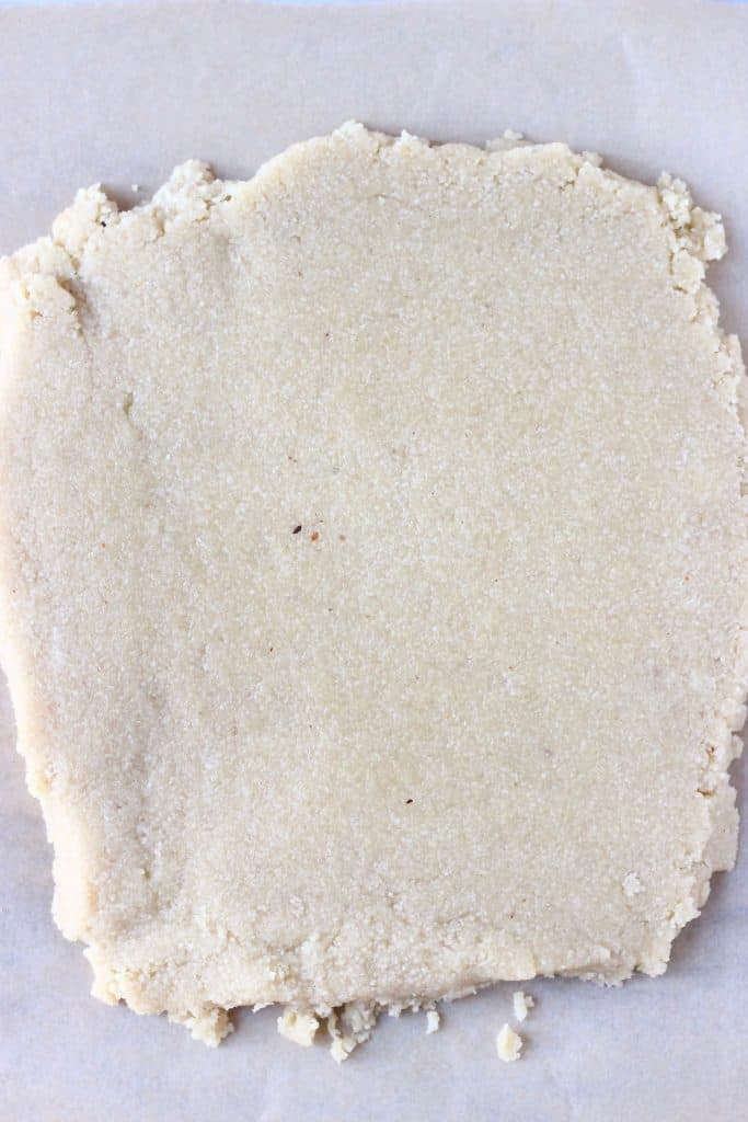 A square of raw shortbread cookie dough rolled out on a sheet of brown baking paper