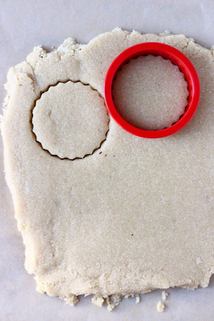 A square of raw shortbread cookie dough rolled out on a sheet of brown baking paper with a red circular cookie cutter cutting out a circle of dough