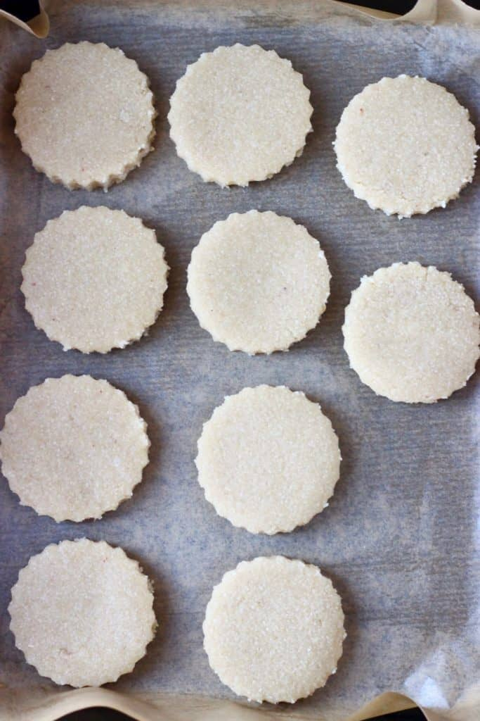 Ten circular raw shortbread cookies on a sheet of brown baking paper