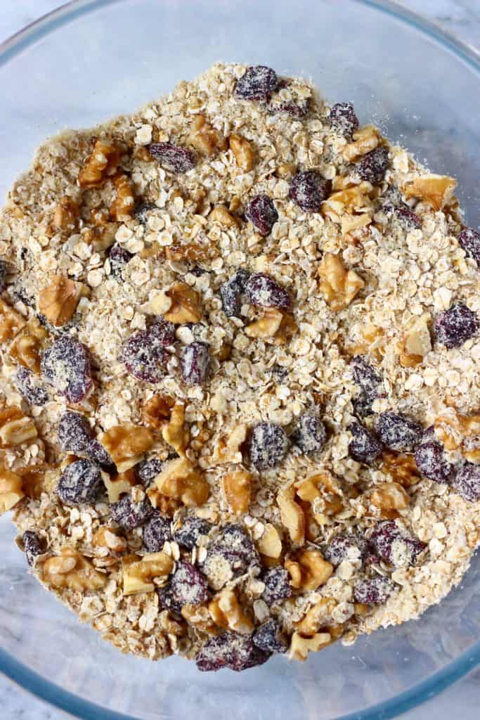 Oats, dried cranberries and chopped walnuts in a glass mixing bowl against a marble background