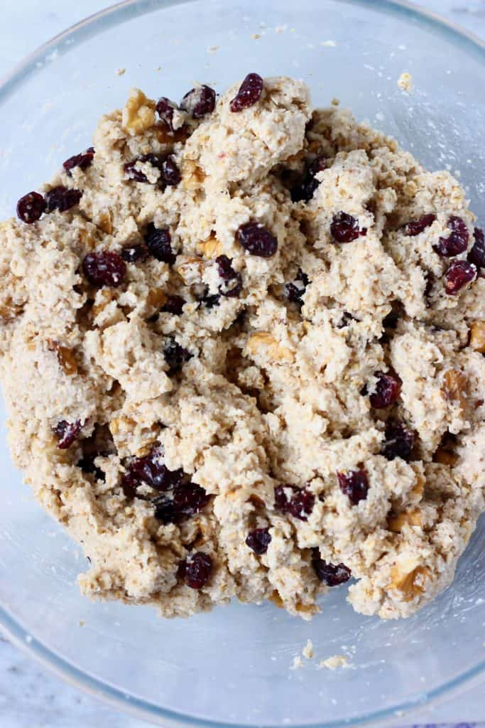 Raw oatmeal bread batter with cranberries and chopped walnuts in a glass mixing bowl against a marble background