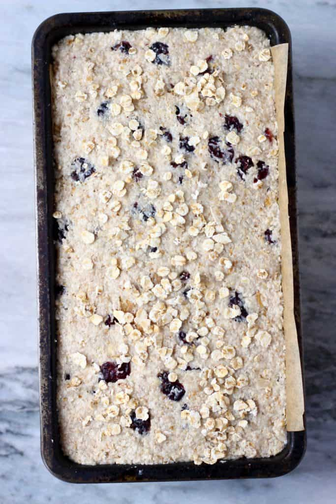 Raw oatmeal bread batter with cranberries and chopped walnuts sprinkled with oats in a black loaf tin against a marble background