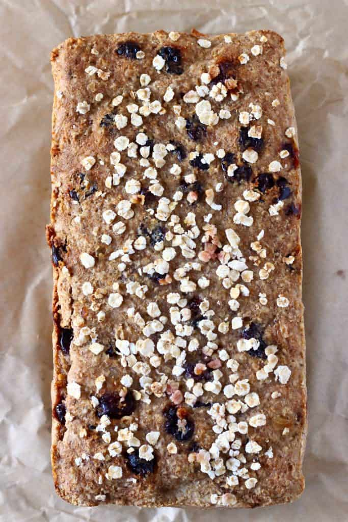 A loaf of brown bread with cranberries sprinkled with oats on a sheet of brown baking paper