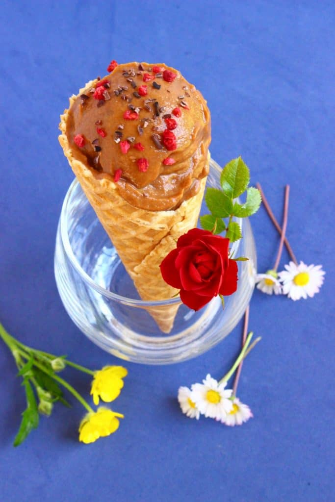 An ice cream cone with a scoop of chocolate ice cream in a glass against a dark blue background scattered with flowers