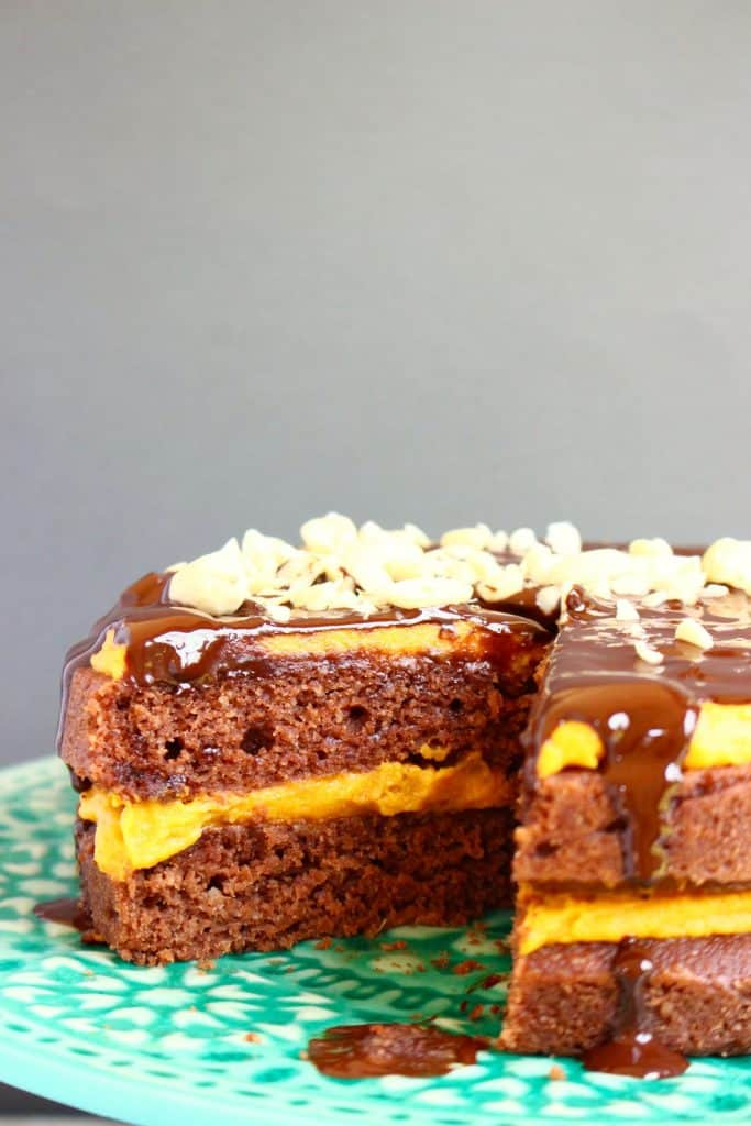 A chocolate cake sandwiched with orange frosting and topped with a chocolate ganache and chopped peanuts on a green cake stand against a grey background