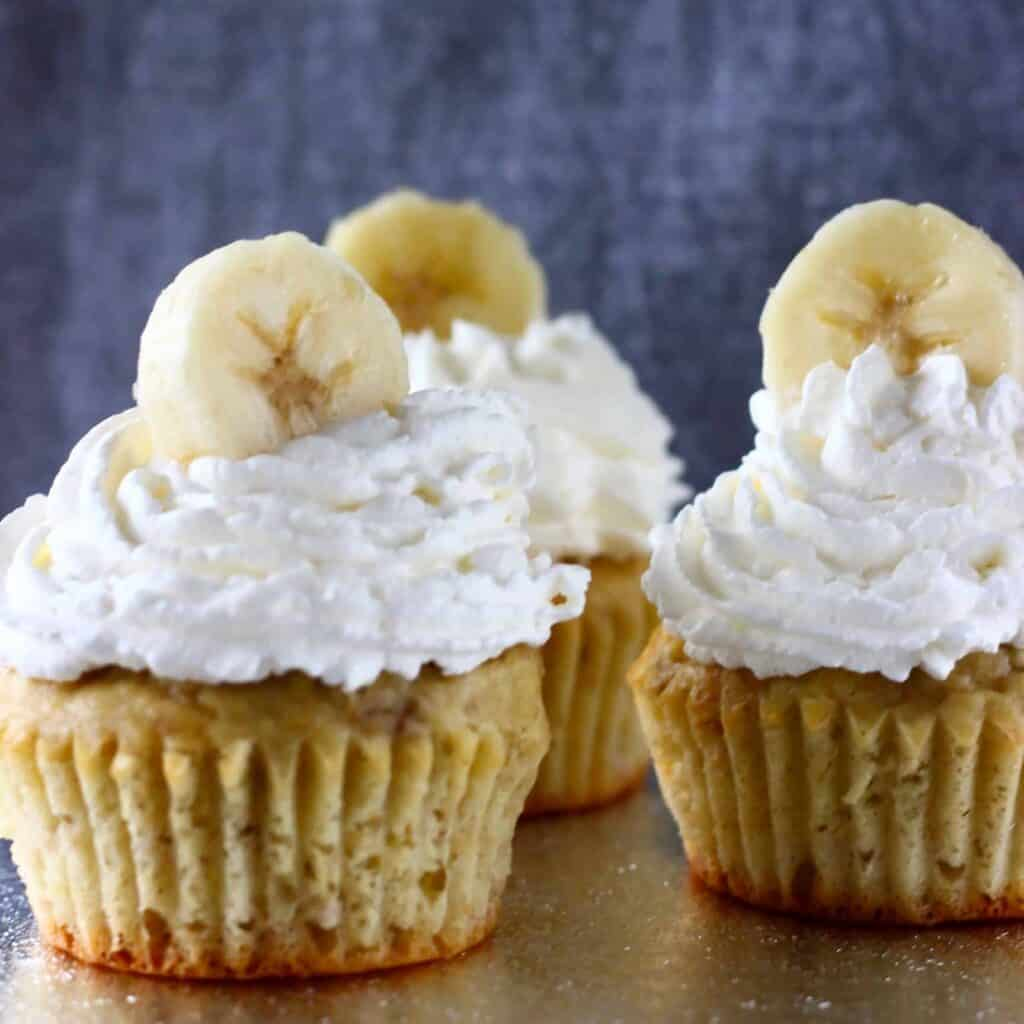 Three banana cupcakes topped with cream and a banana slice each on a silver board against a grey background