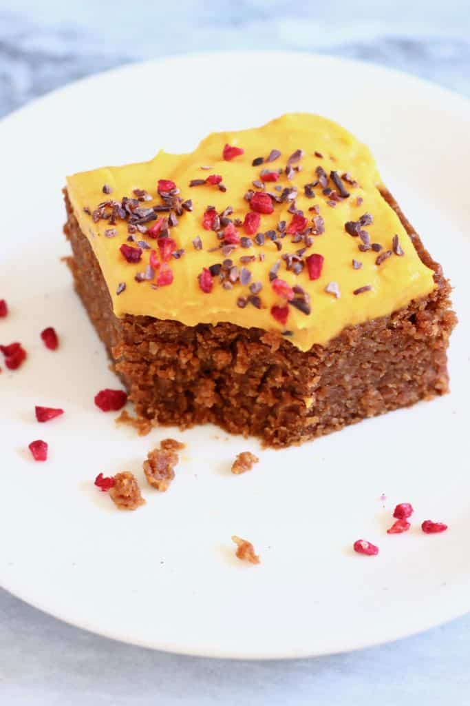 A square of chocolate sponge cake topped with yellow frosting sprinkled with cacao nibs and freeze-dried raspberries with a mouthful taken out of it on a white plate against a marble background