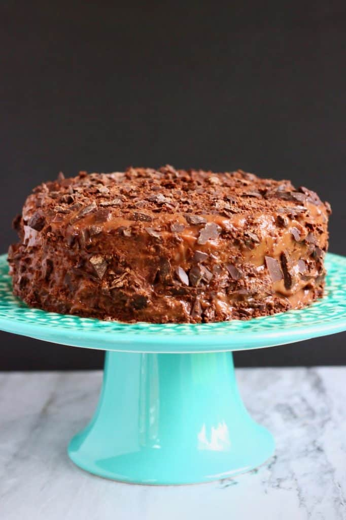 A chocolate cake covered with frosting and chocolate pieces on a green cake stand against a black background