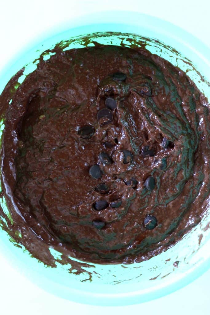 Raw chocolate banana bread batter with chocolate chips in a mixing bowl