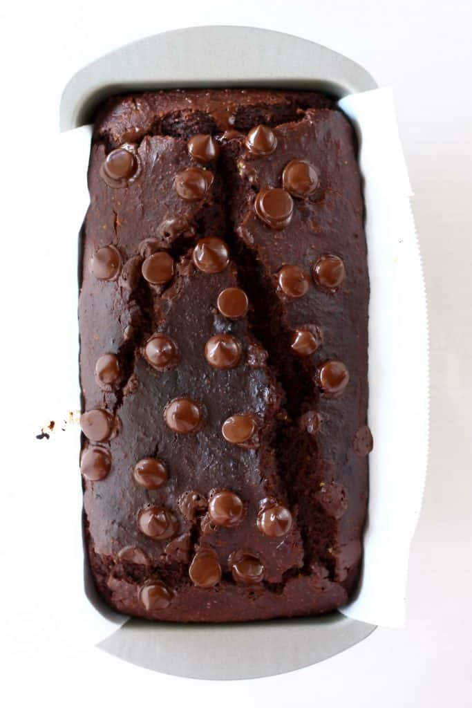 A loaf of baked chocolate banana bread topped with chocolate chips in a loaf tin