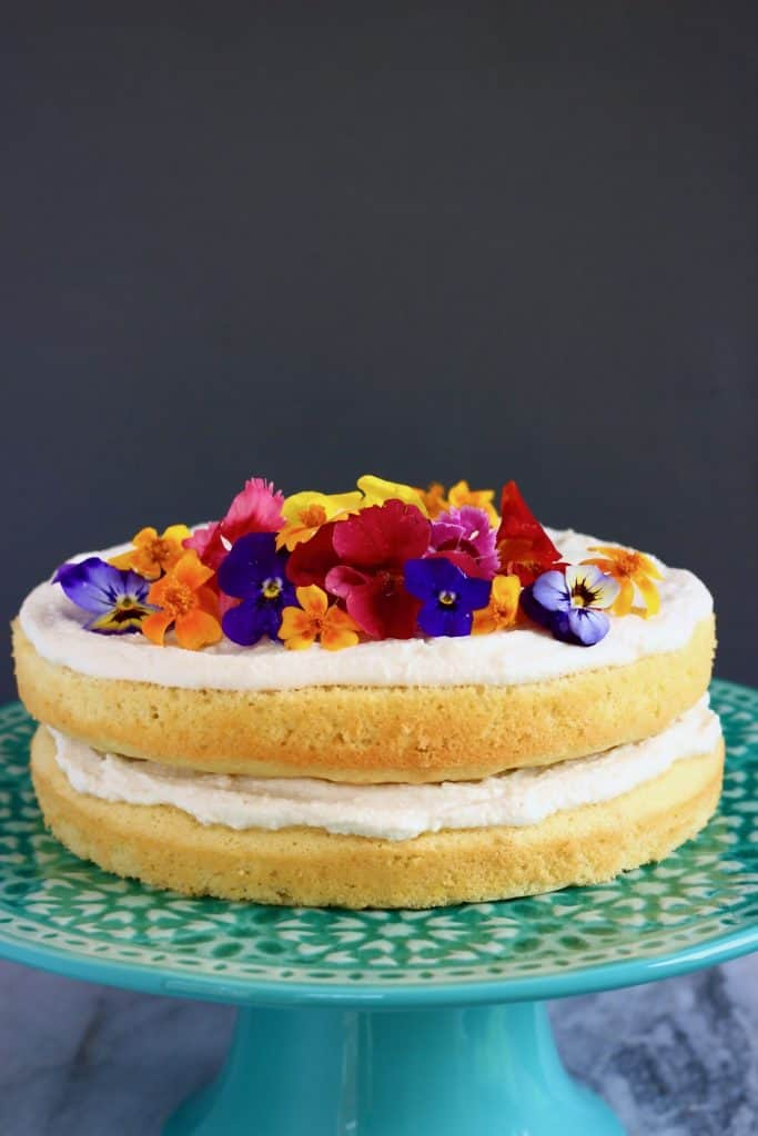 A sponge cake layered with white creamy frosting and topped with colourful edible flowers on a green cake stand against a grey background