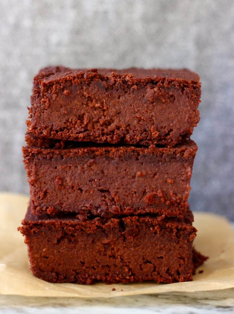 Photo of three chocolate brownies stacked on top of each other on a piece of brown baking paper against a grey background