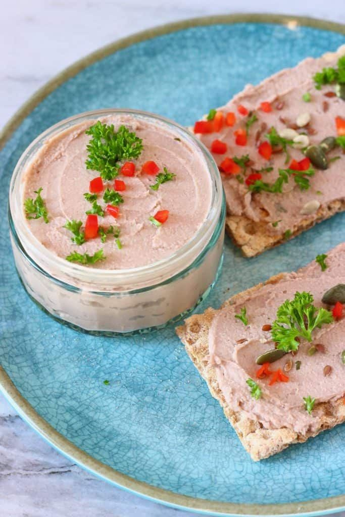 Photo of a glass pot filled with beige pâté topped with herbs and chopped red pepper on a blue plate with two rectangular crackers spread with pâté and decorated with pumpkin seeds, chopped red chilli and green herbs