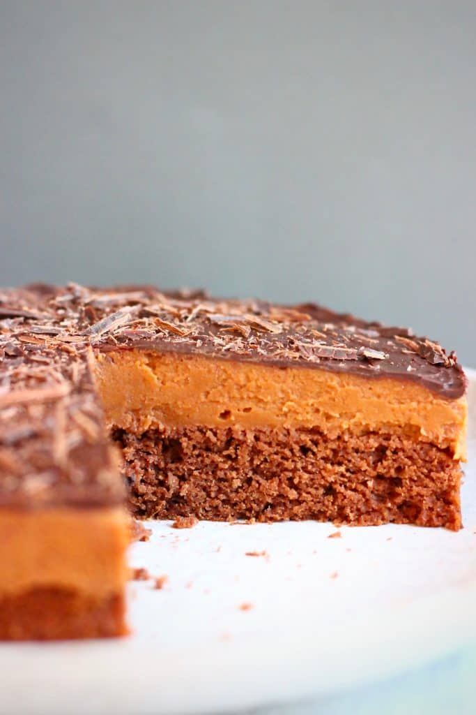 Photo of chocolate sponge topped with chocolate mousse and chocolate ganache against a grey background