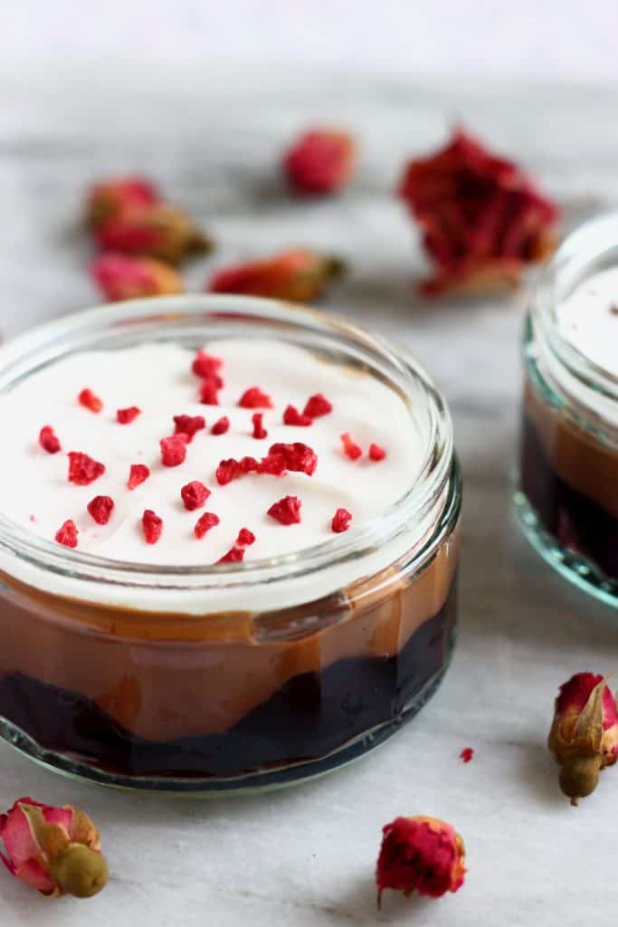 Photo of a trifle in a glass ramekin made with cherries, chocolate custard and topped with white cream and freeze-dried raspberries against a marble background scattered with dried roses