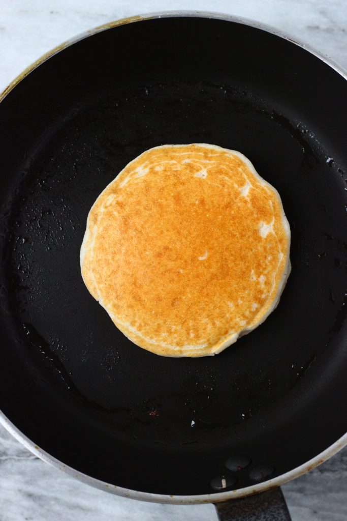 A golden brown coconut flour pancake being cooked in a black frying pan against a marble background