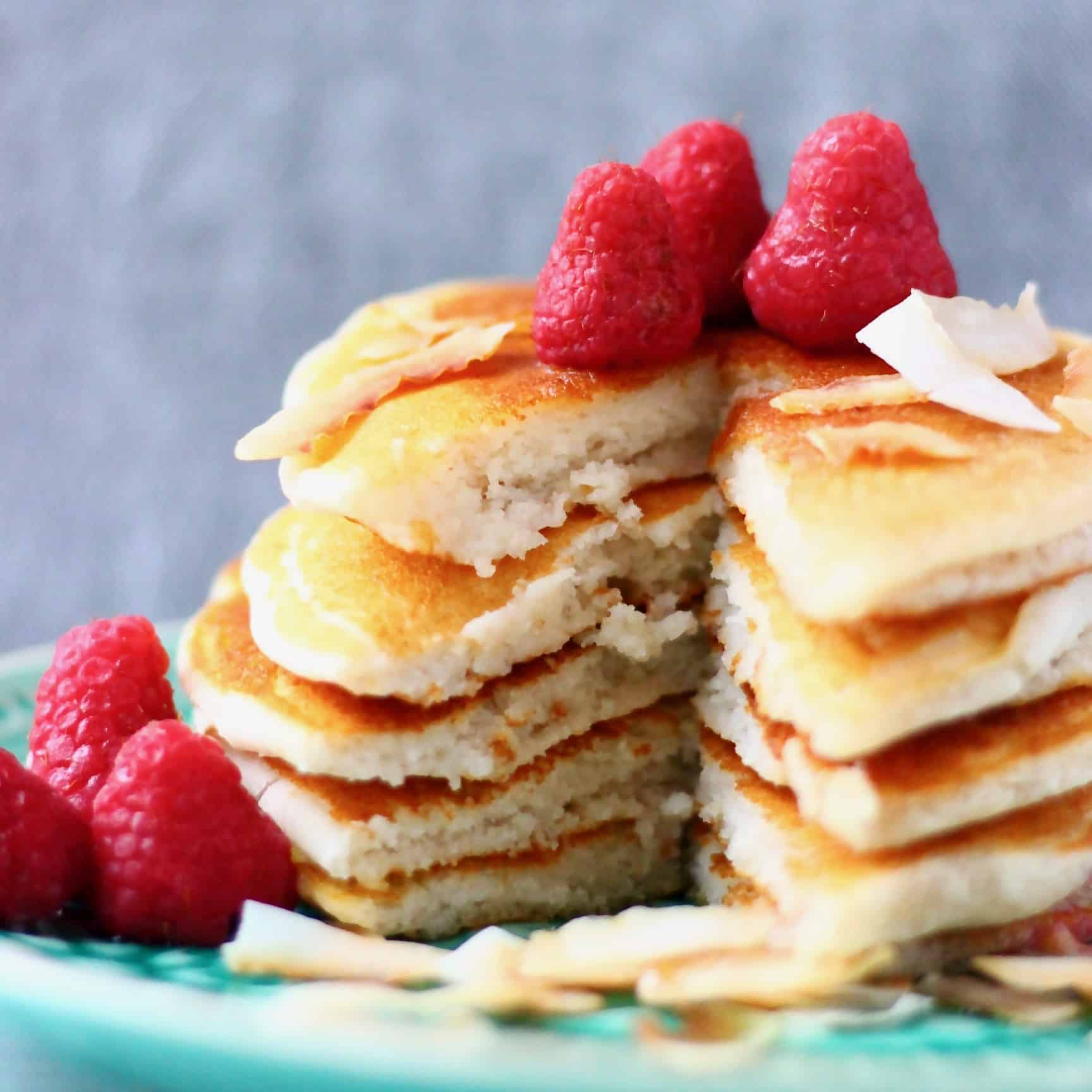 Five coconut flour pancakes stacked in a pile decorated with fresh raspberries and coconut flakes on a green plate against a grey background