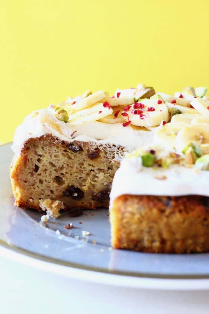A sliced banana cake on a green plate topped with white frosting, banana slices and chopped pistachios against a yellow background