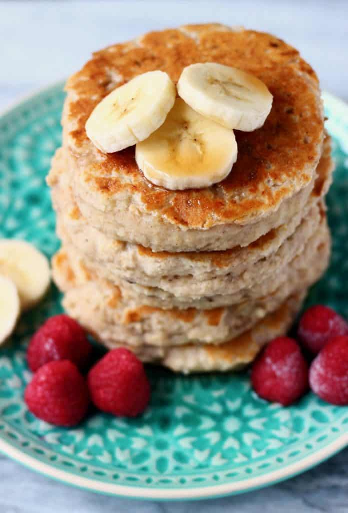Stack of five banana pancakes topped with banana slices on top on a green plate with raspberries against a marble background