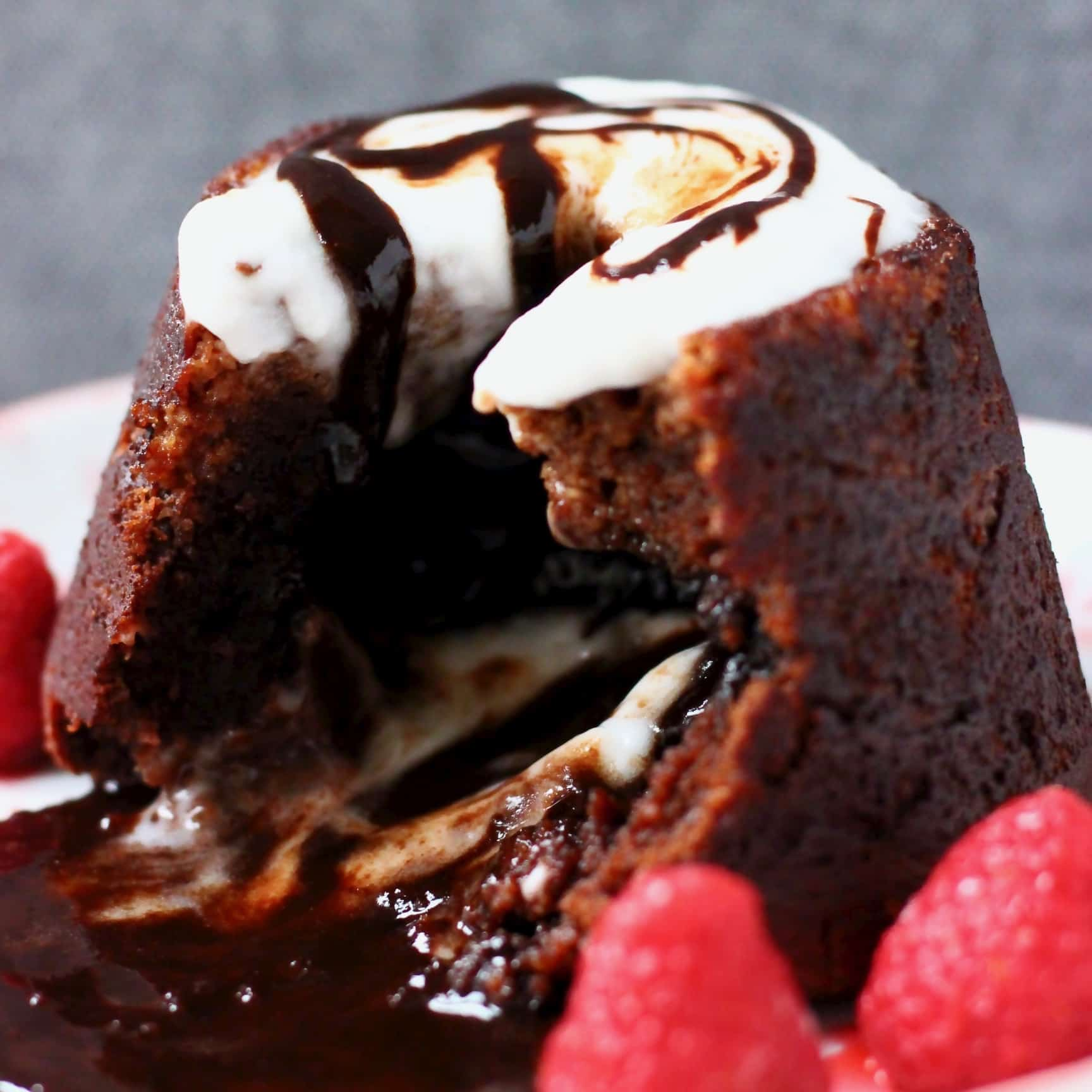 Chocolate lava cake on a plate with chocolate sauce flowing out of it topped with white cream and decorated with raspberries against a grey background