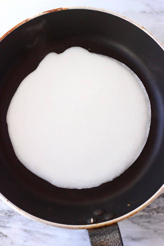 A round crepe being fried in a black frying pan against a marble background