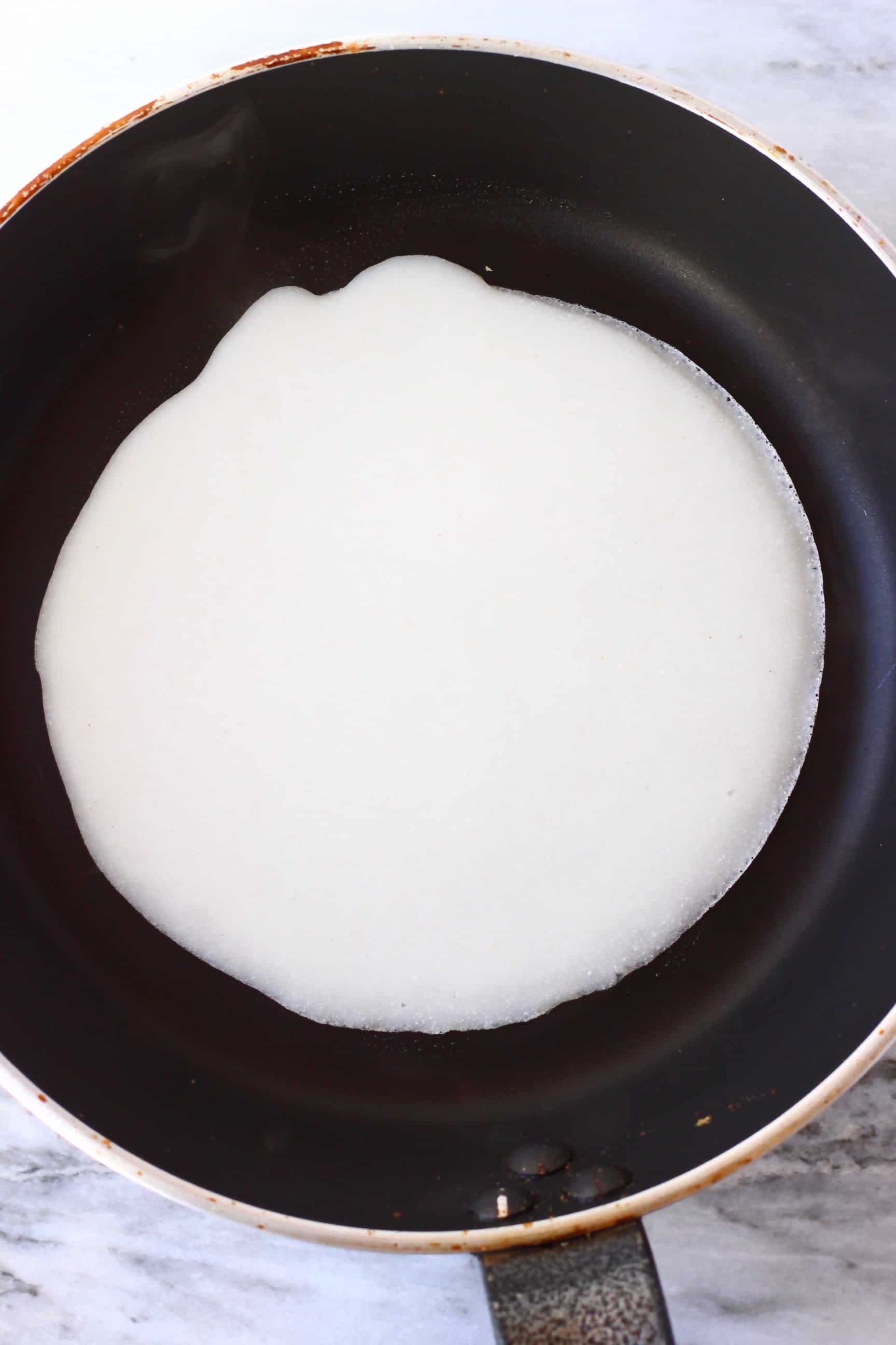A round gluten-free vegan crepe being fried in a black frying pan