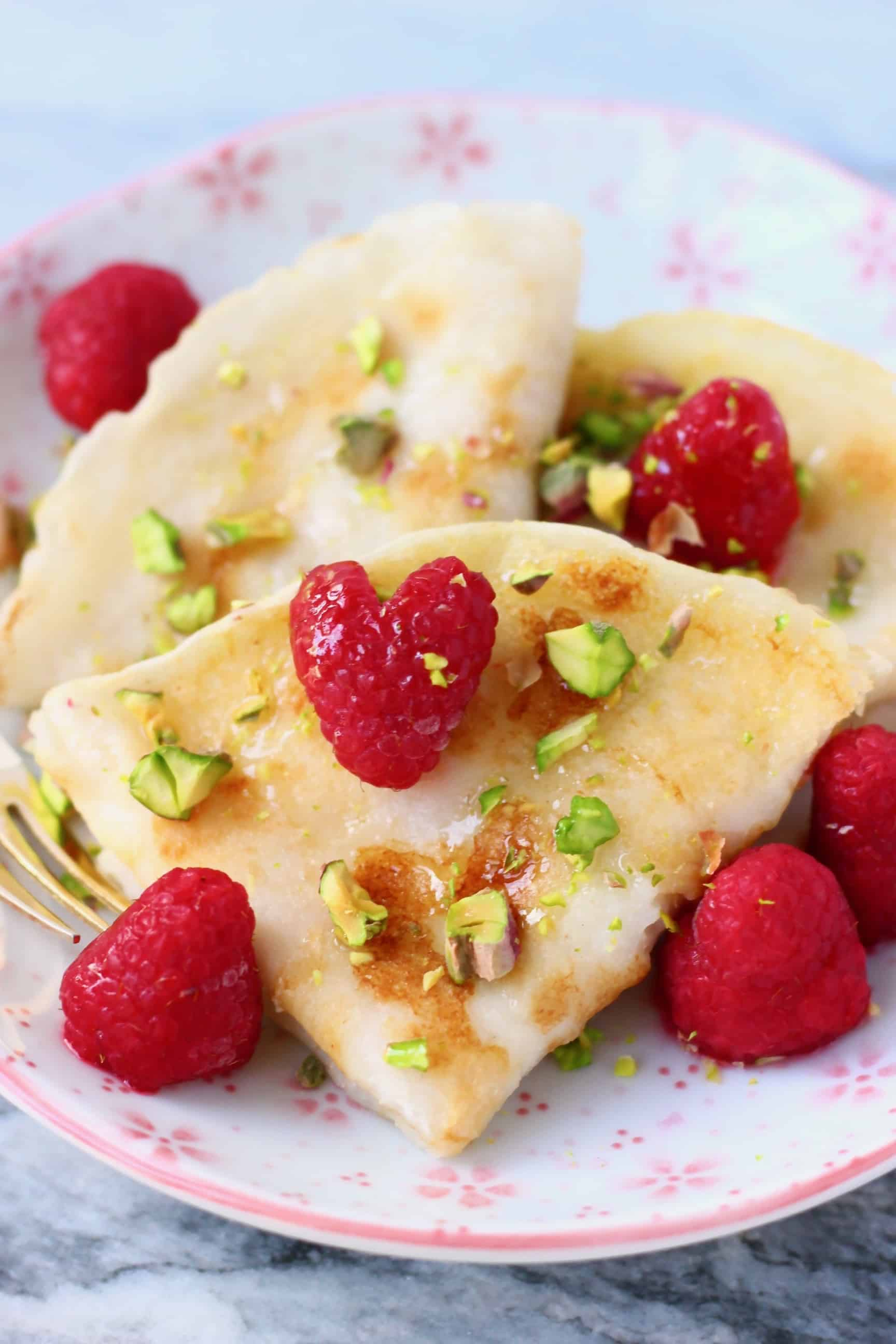 Three folded crepes on a white plate with pink flowers decorated with fresh raspberries and chopped pistachios with a gold fork against a marble background