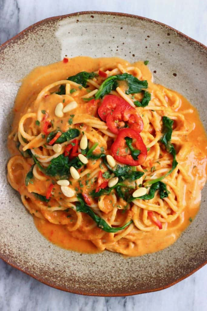 Spaghetti in a creamy red sauce topped with green spinach, sliced red peppers and pine nuts on a dark brown plate against a marble background