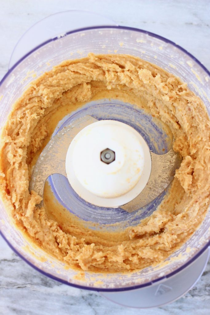 Brown cookie dough in a food processor against a marble background