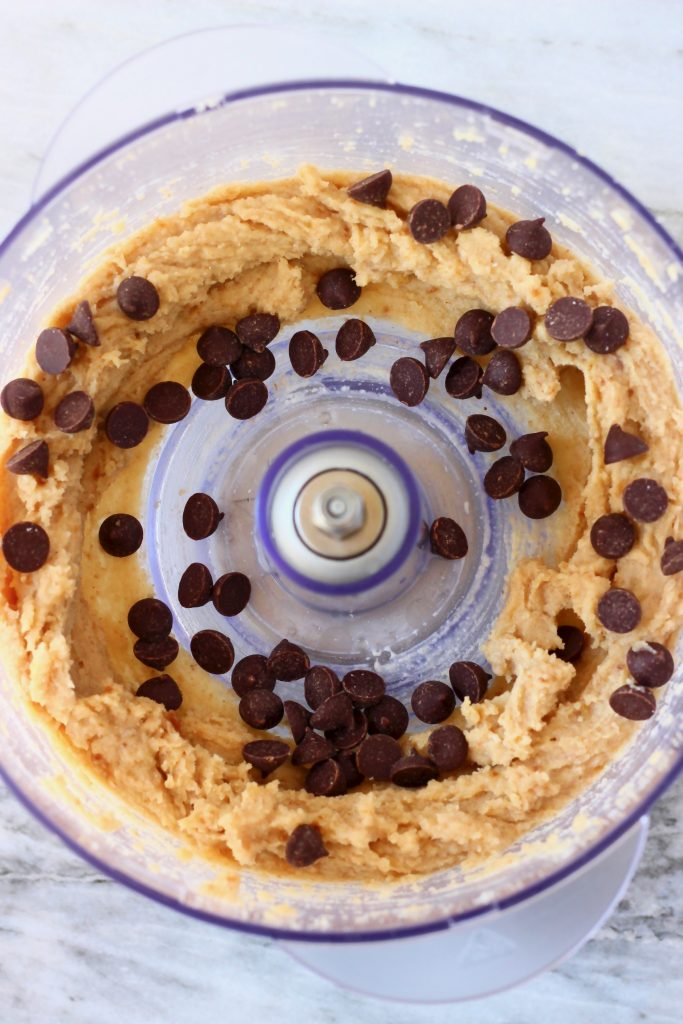 Brown cookie dough and chocolate chips in a food processor against a marble background
