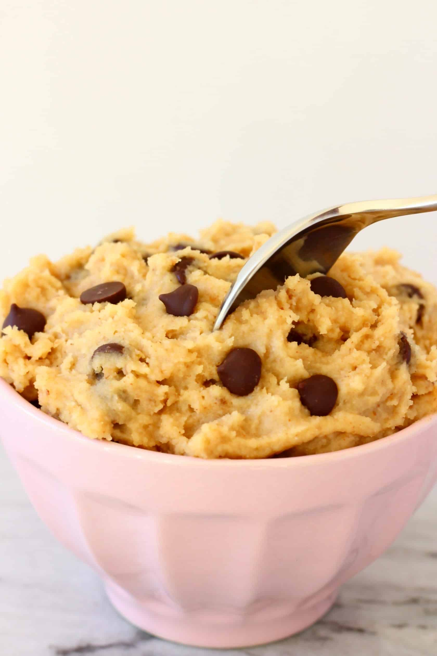 Vegan cookie dough with chocolate chips in a bowl with a spoon sticking into it