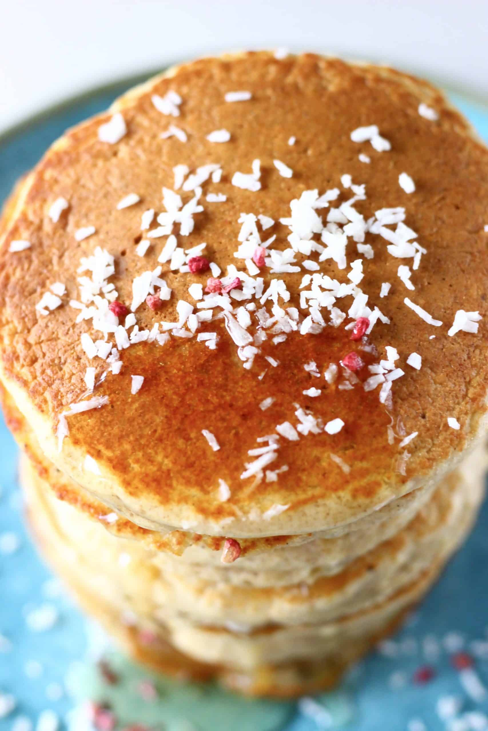 A stack of golden brown pancakes topped with desiccated coconut and syrup on a blue plate