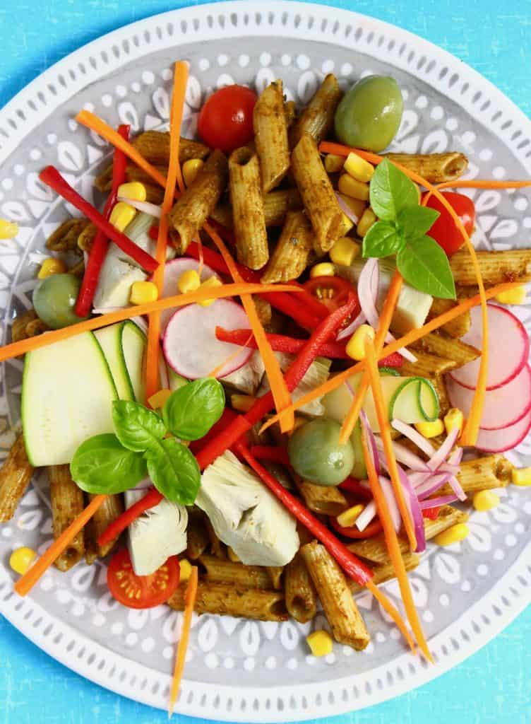 Penne pasta in sundried tomato pesto with colourful vegetables on a light grey plate against a blue background