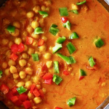 Red curry sauce with chickpeas, red peppers and green peppers in a black pan against a white background