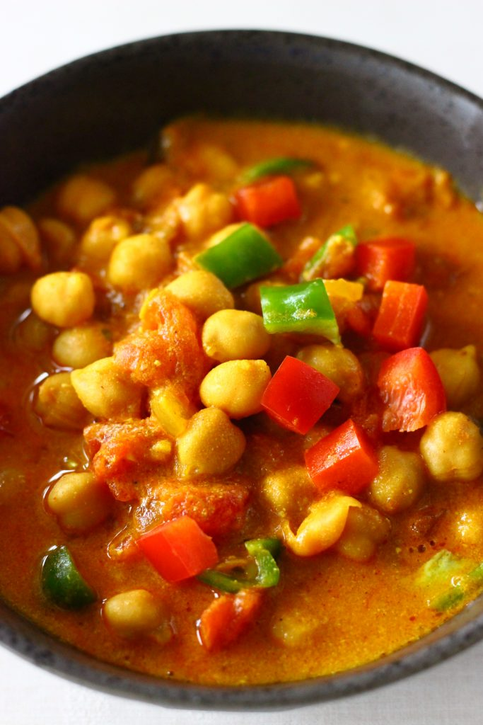 Red curry sauce with chickpeas, red peppers and green peppers in a black bowl against a white background