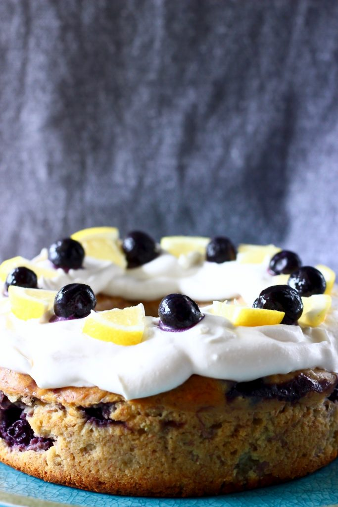 A round bundt cake topped with white creamy frosting, lemon slices and fresh blueberries against a grey background